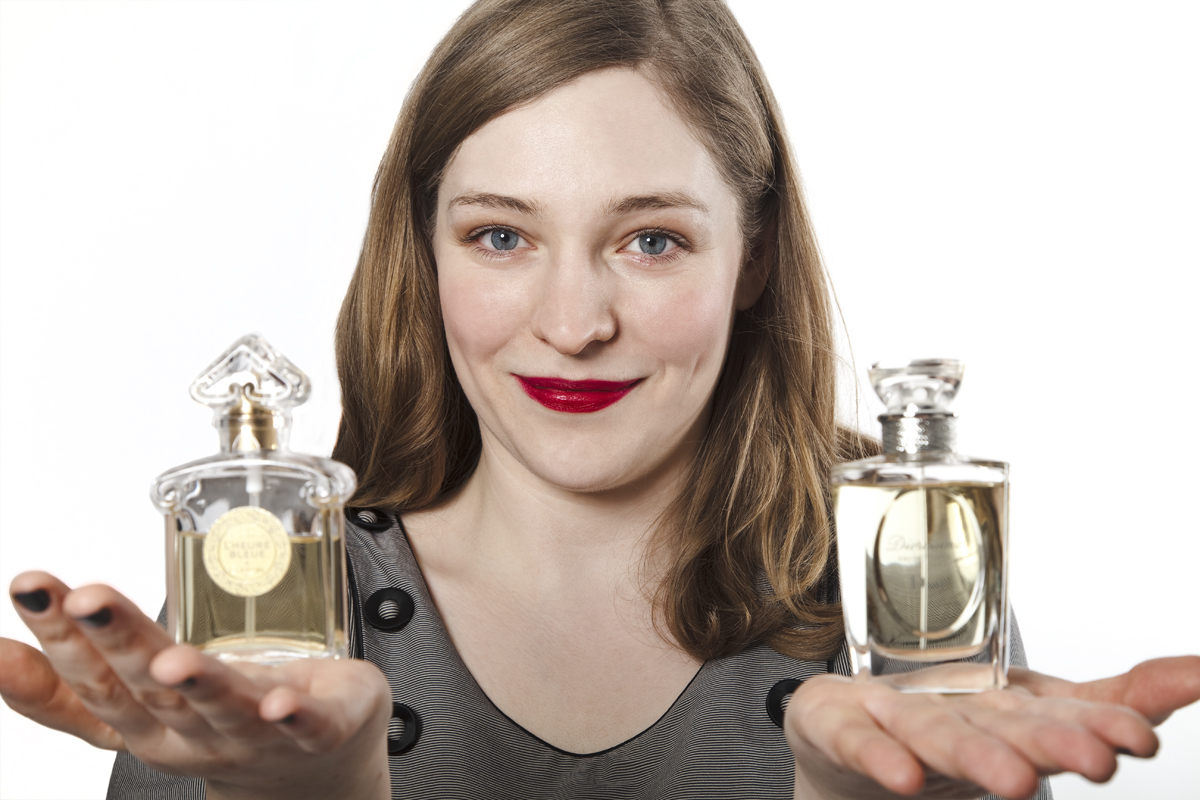 A woman with red lipstick holding two perfume bottles