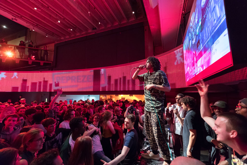 A rapper performing to a large enthusiastic crowd in a museum under hot pink light