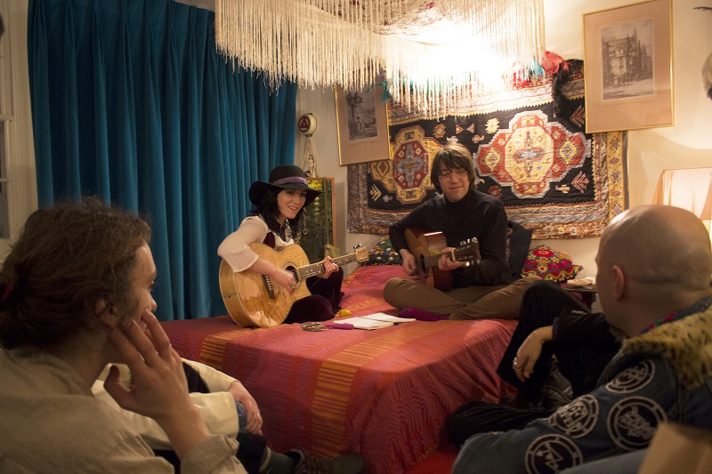 A group of people in 1960s costume playing music together in a bedroom