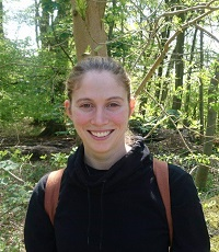 A woman smiling, wearing a rucksack, standing in a forest