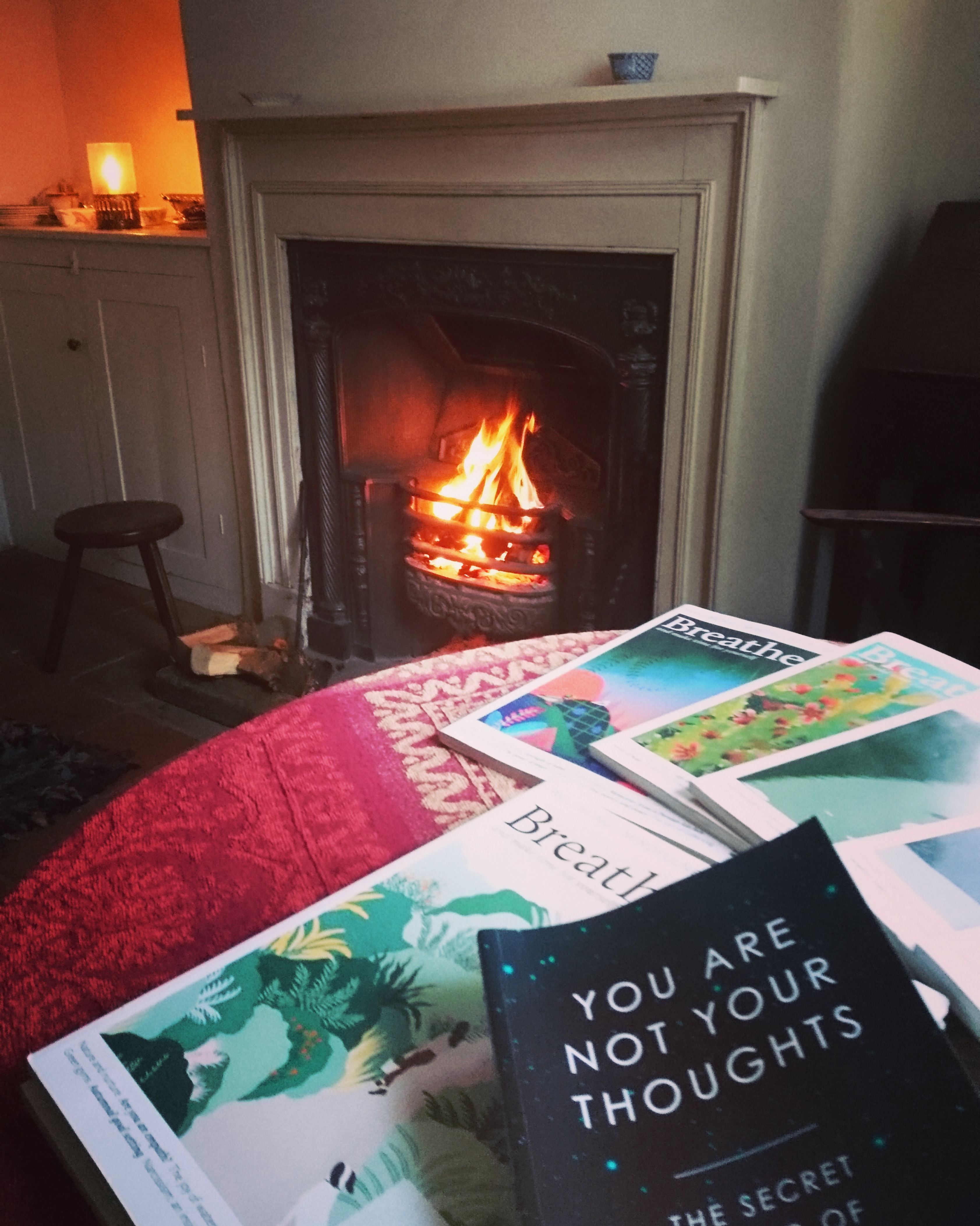 Mindfulness guidebooks on a table in a cottage in front of a cosy fire