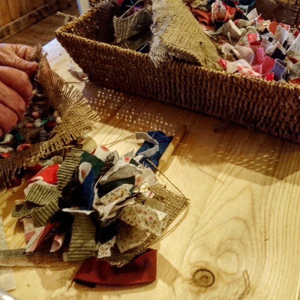 A closeup of hands using scraps of fabric to create a rag rug